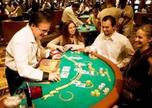a male casino dealer laughing with his customers
