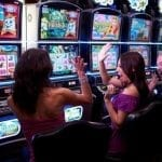two women cheering in front of slot machines