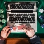 a man placing poker chips near his laptop