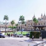 monte carlo at day with the most famous casino in monaco, tjere's a car and kids running around
