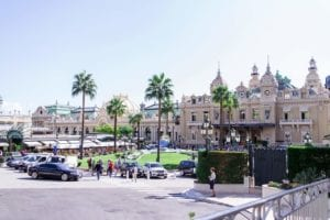 monte carlo at day with the most famous casino in monaco, tjere's a car and kids running around The Lucky City