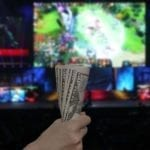 a hand holding money woth gaming screen on the background