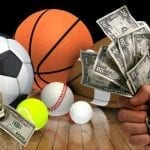 sports balls laying on the floor with a hand holding a couple of dollars